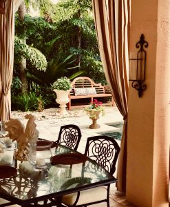 View of decorative bench through cabana drapes and dining table and chairs