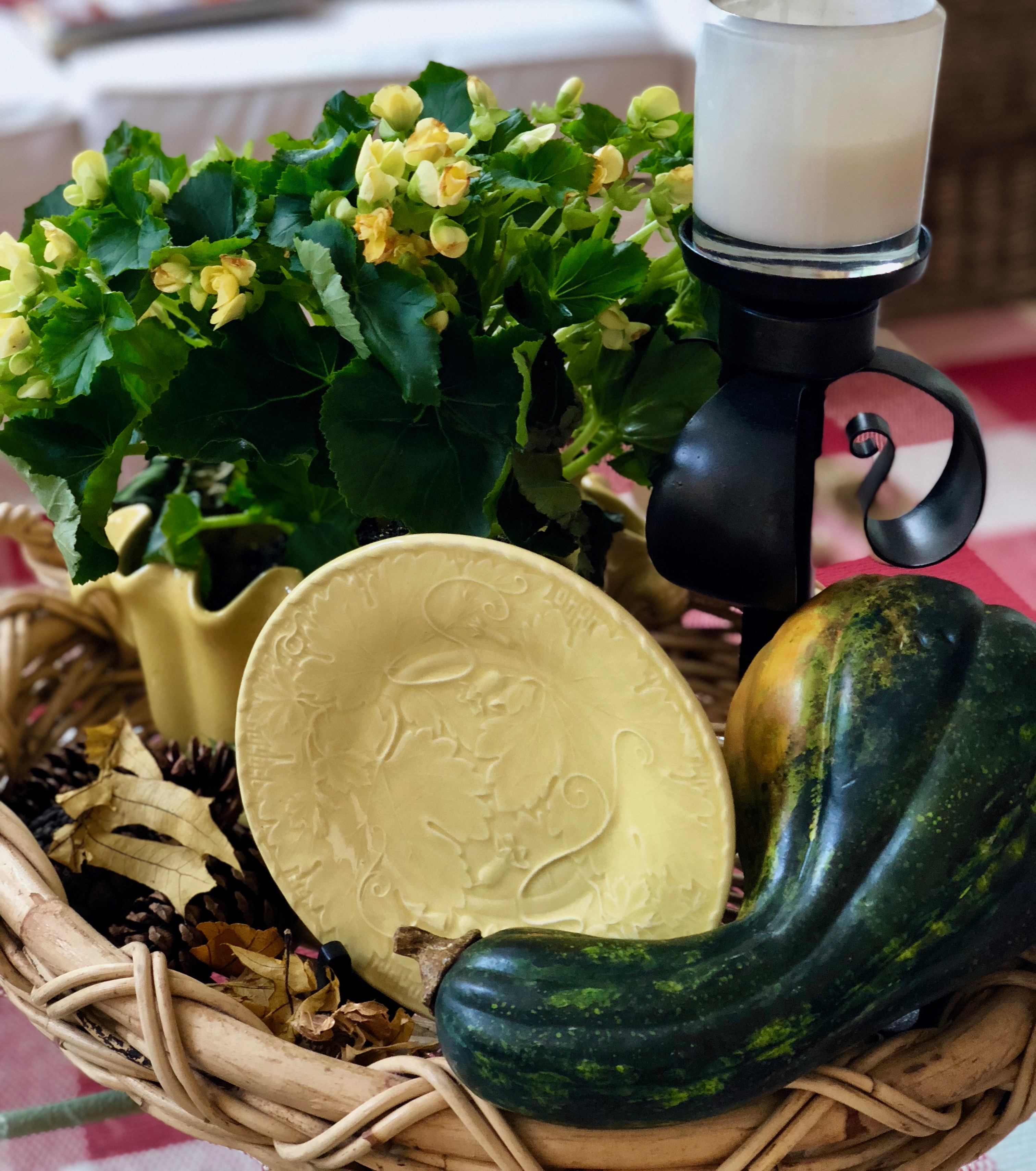Squash with decorative plate and leaves. Candle and yellow begonia plant. All of this is on a large tray