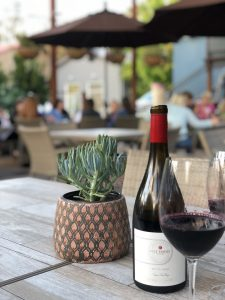 Wine bottle with glass and succulent in foreground. Families and couples under the umbrellas on the patio