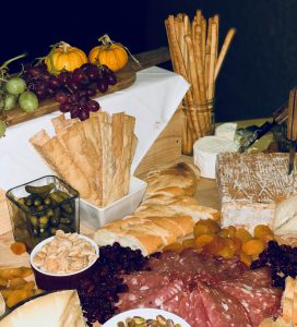 Large cheese platter with selection of meats, olives and nuts