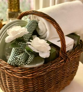 Picnic basket with plates, green gingham napkins and floral napkin rings