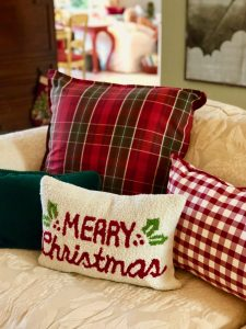 Merry Christmas and buffalo plaid pillows on living room sofa