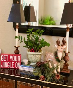 Get your Jingle On sign with plant and lamps. Reindeer and books finish the look