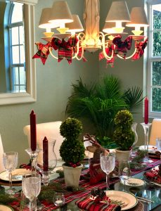 Christmas Table Setting With Topiaries . Bows On The Chandelier