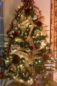 Tall shot of entire tree decorated with white lights, burlap and tartan accents