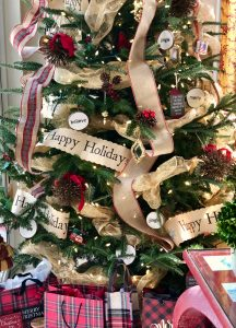 Rustic decor on Christmas Tree including ornaments with Believe, Jingle and Merry. Also, burlap and tartan accents