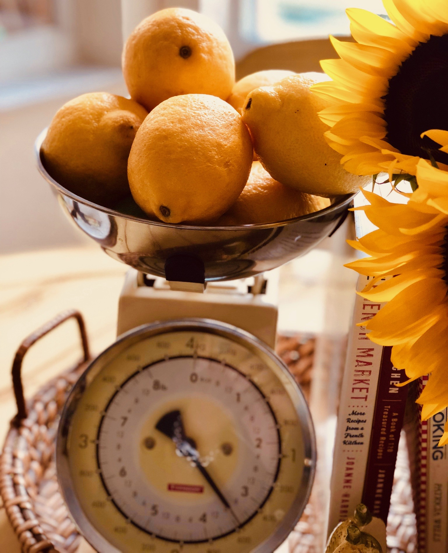 Vintage food scale with fresh lemons and sunflowers on a tray