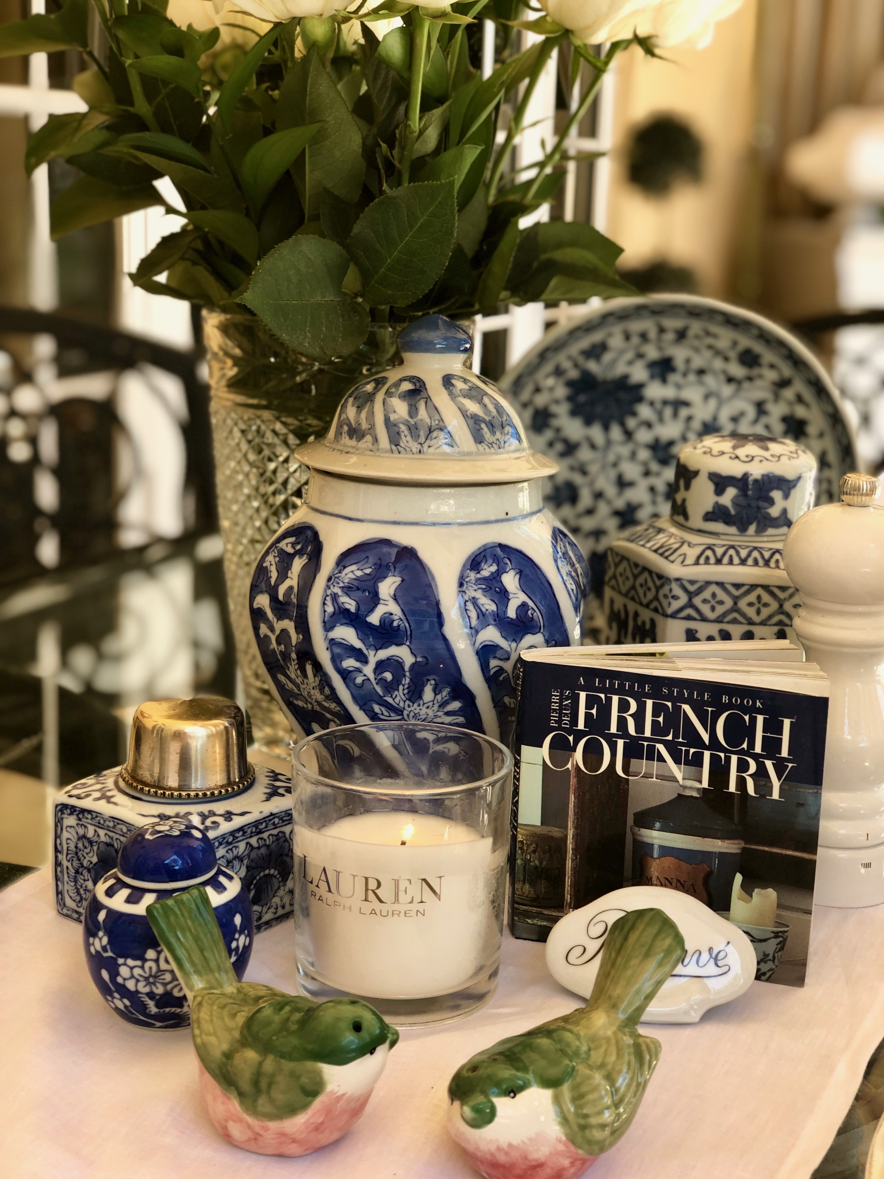 Blue and white table setting on the patio with book, candle and other ceramics
