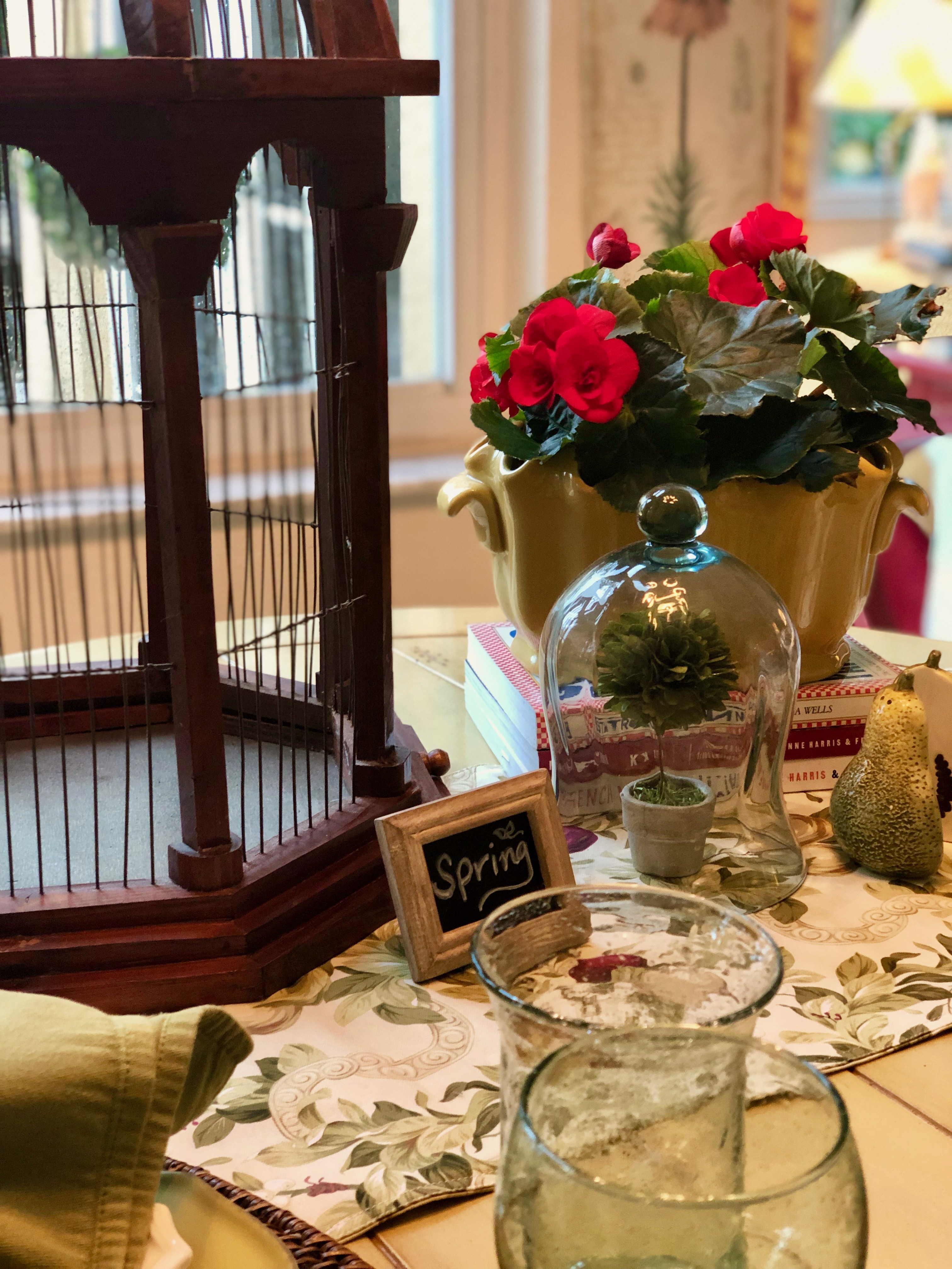 "Table setting with greens and reds and a large birdcage. Also, a cloche in the foreground and a miniature chalkboard with ""spring"" written on it"