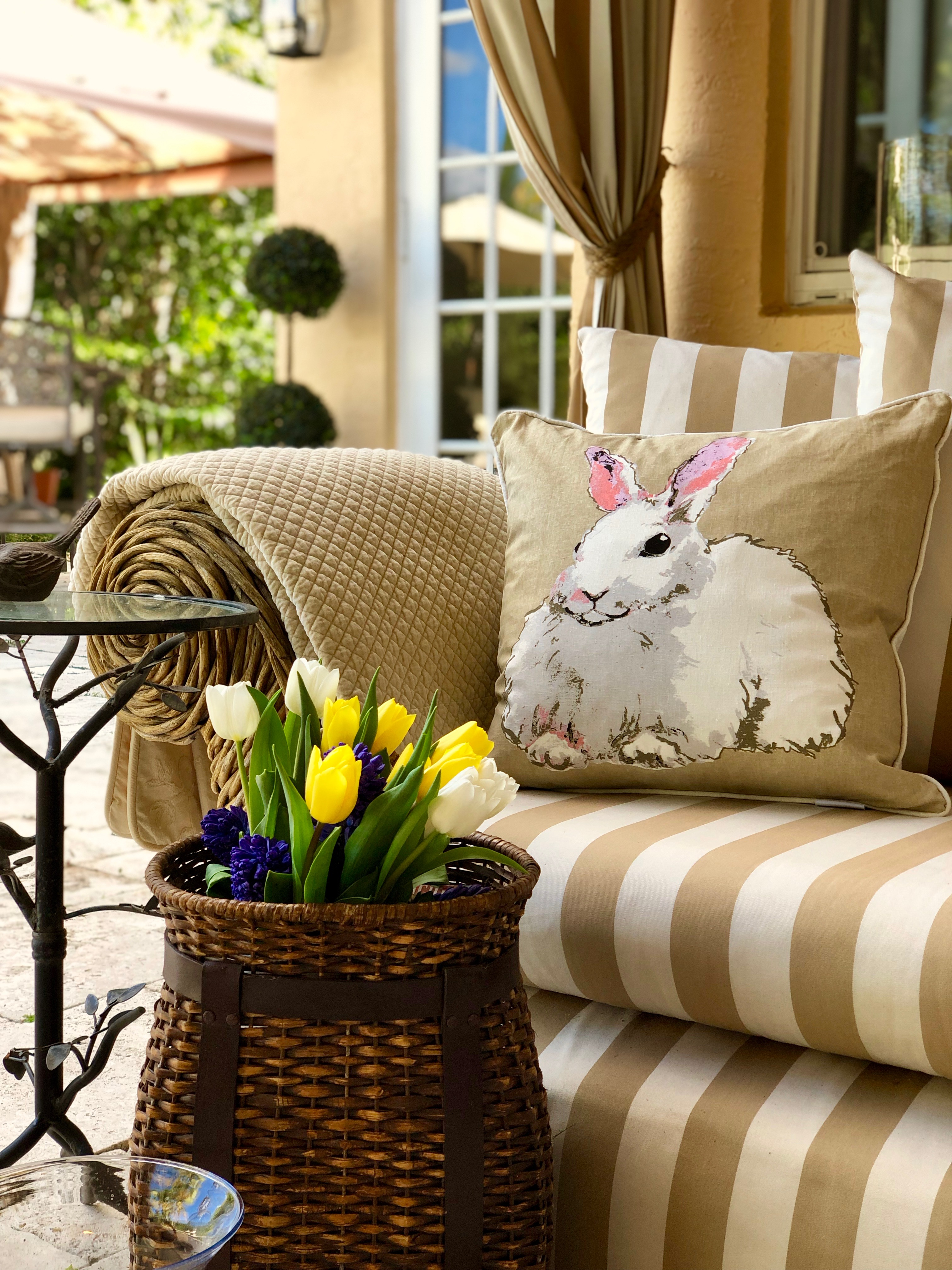Taupe and white striped chaise with a bunny pillow , fresh tulips and a comfy throw