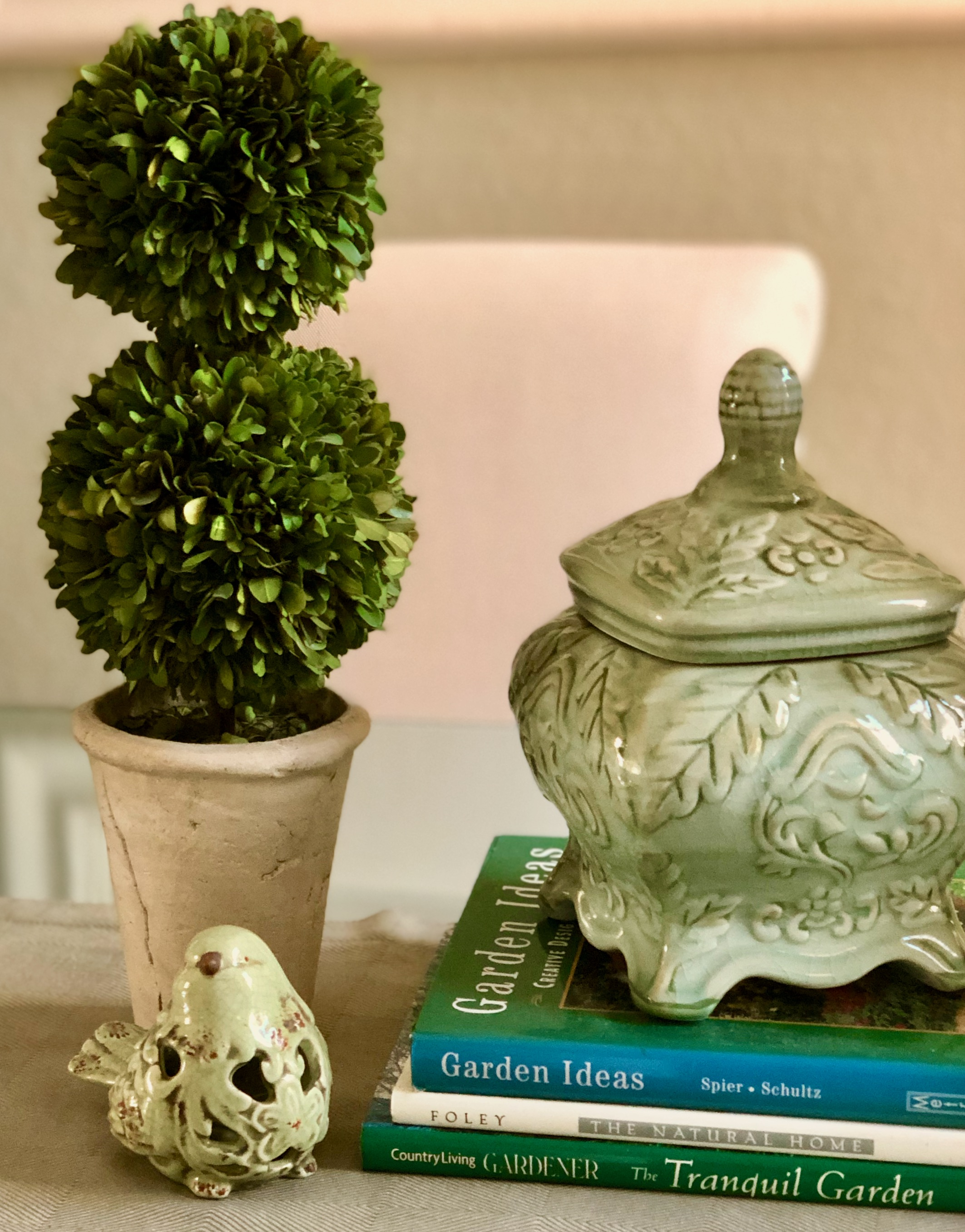 Green pottery with topiary and stack of books