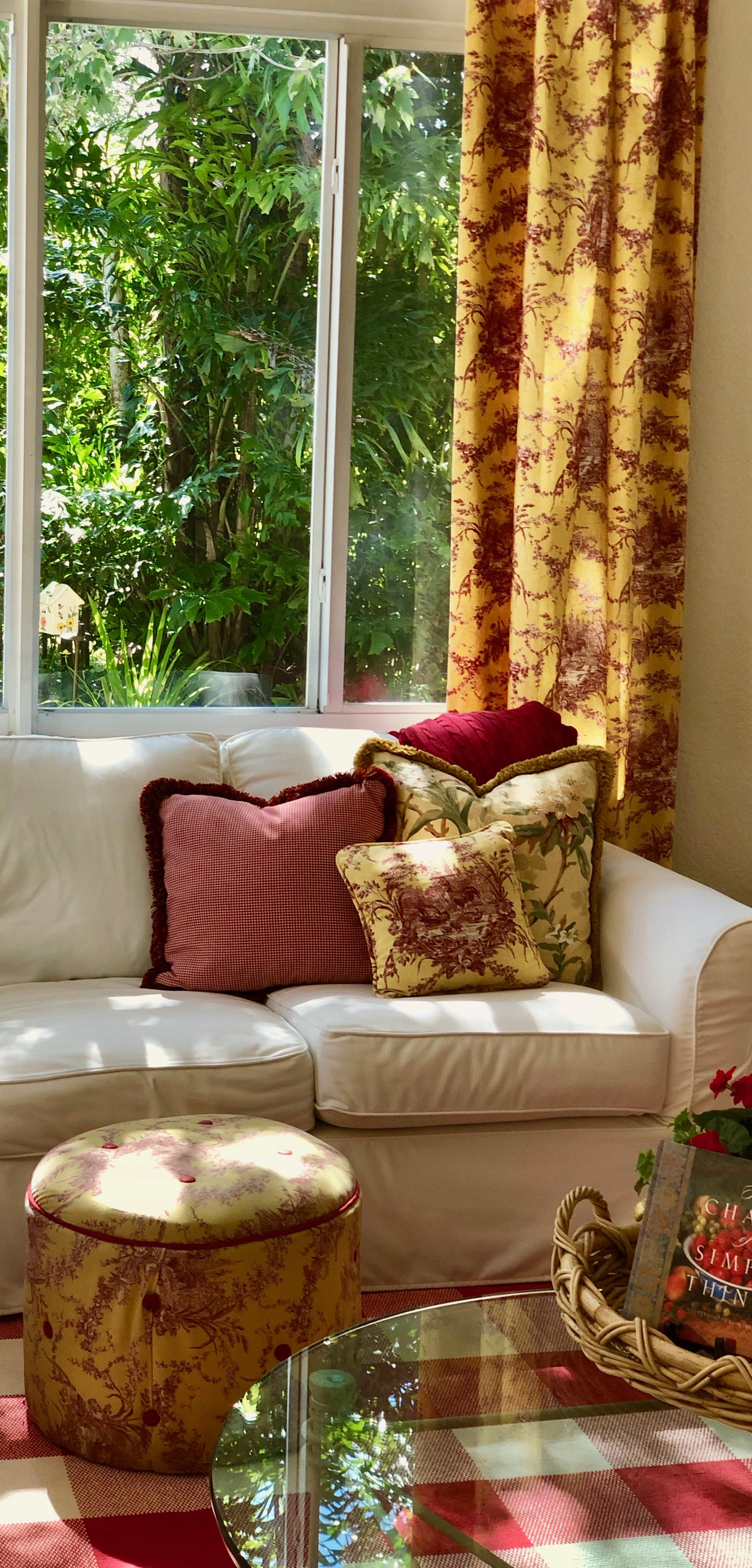 White slipcovered couch with red and yellow Waverly brand toile fabric curtain panels, ottoman and accent pillow. Iron with glass top table and tray with a colorful vignette