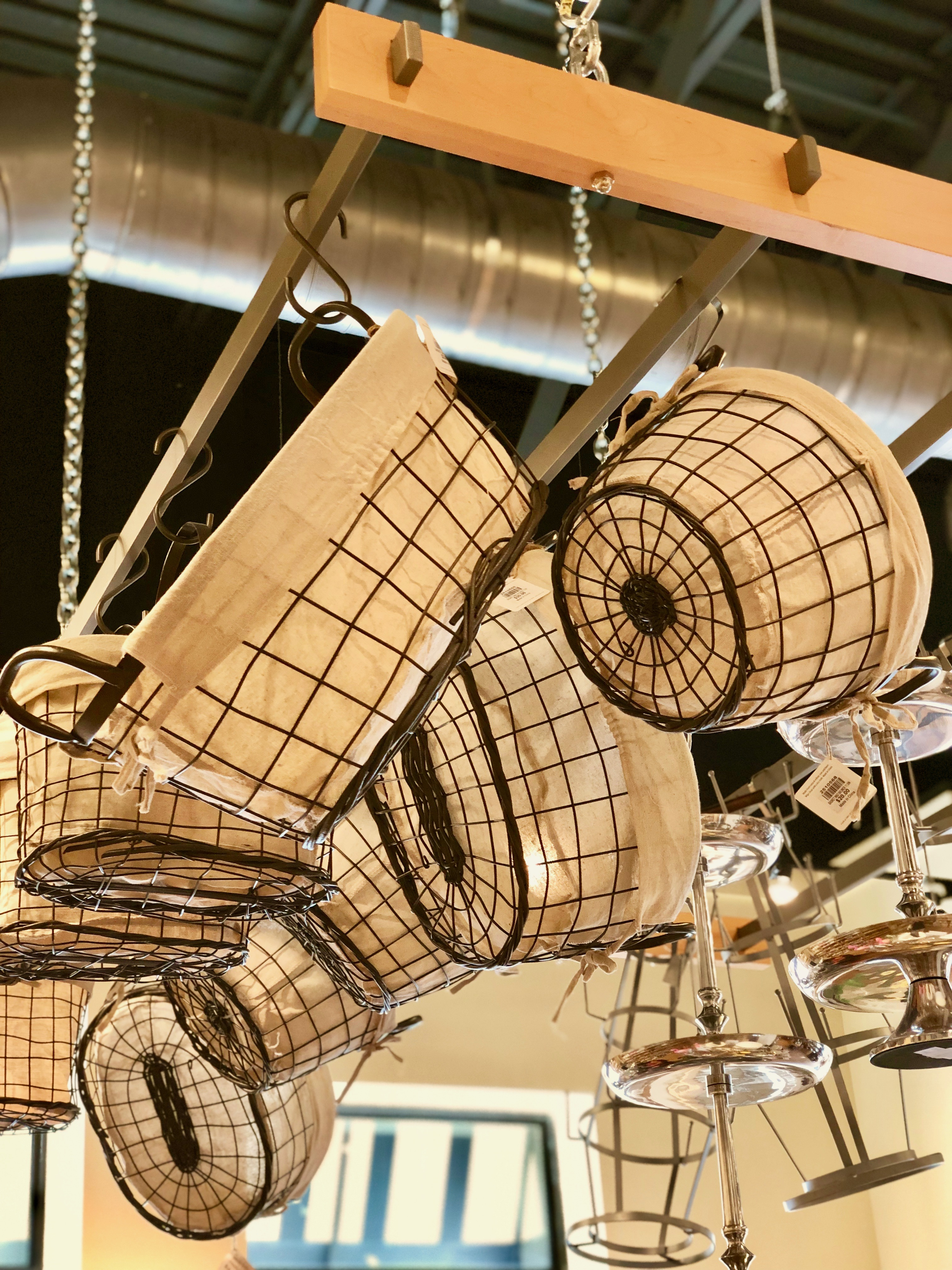 Large wire serving baskets hanging from the ceiling on a hanging rack