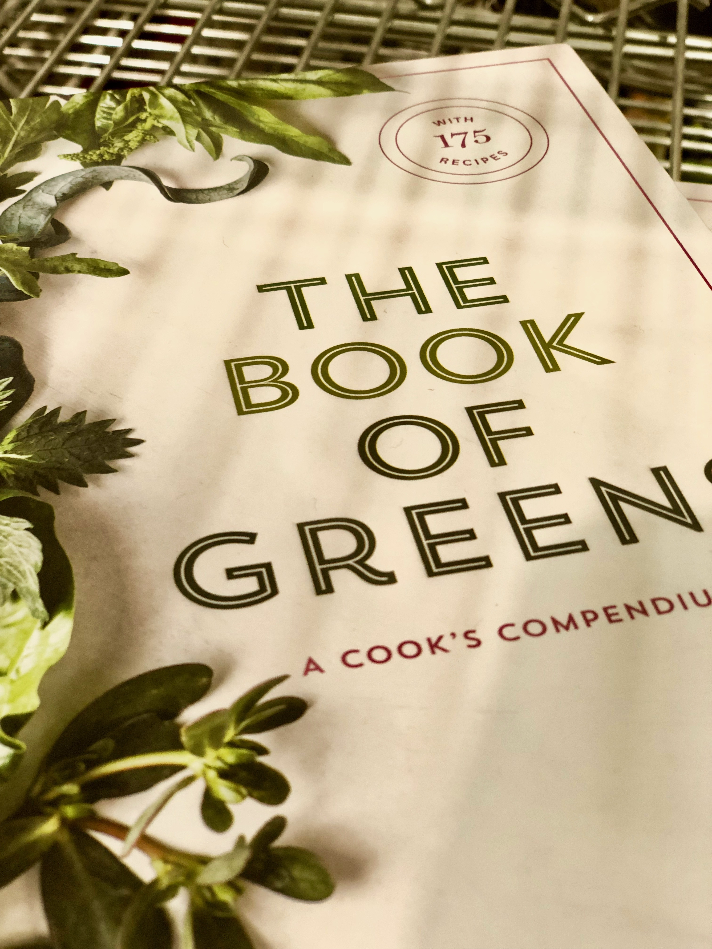 A picture of the Book of Green Cook Book on a shelf in Sur La Table store