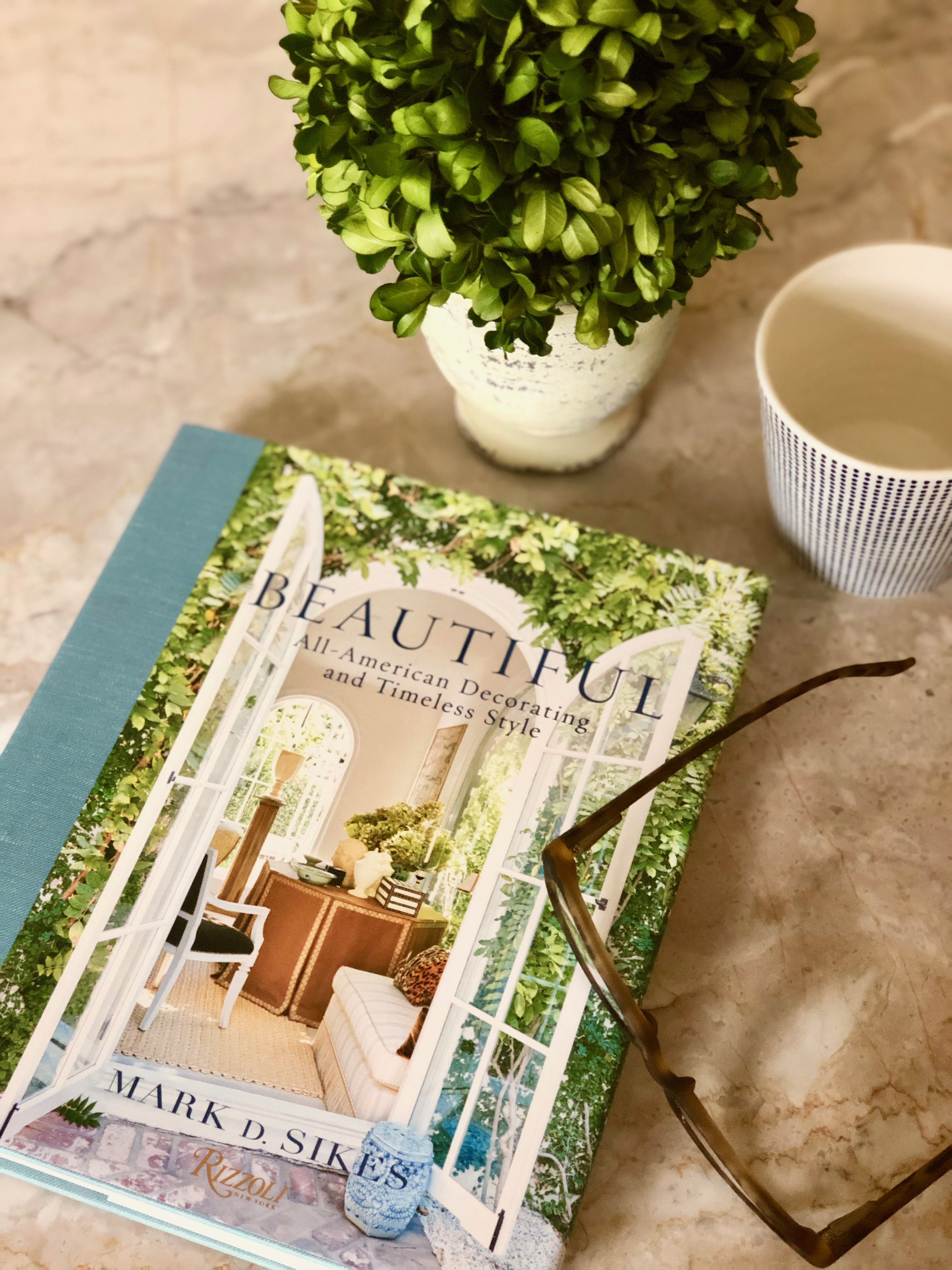 Mark D Sikes book Beautiful on our kitchen island with a cuppa and a small topiary