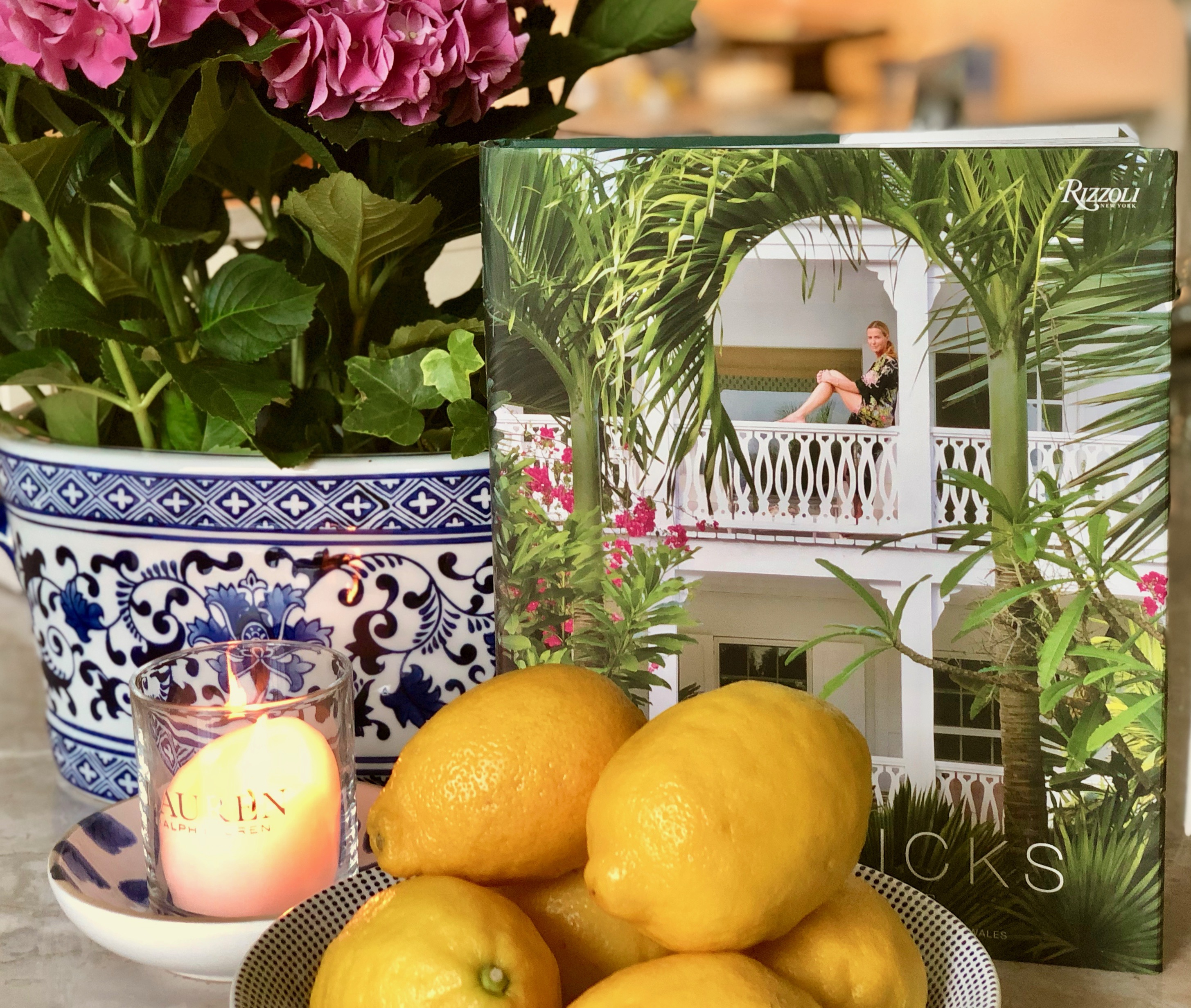 India Hicks decorating book with a bowl of lemons and a hydrangea in the background