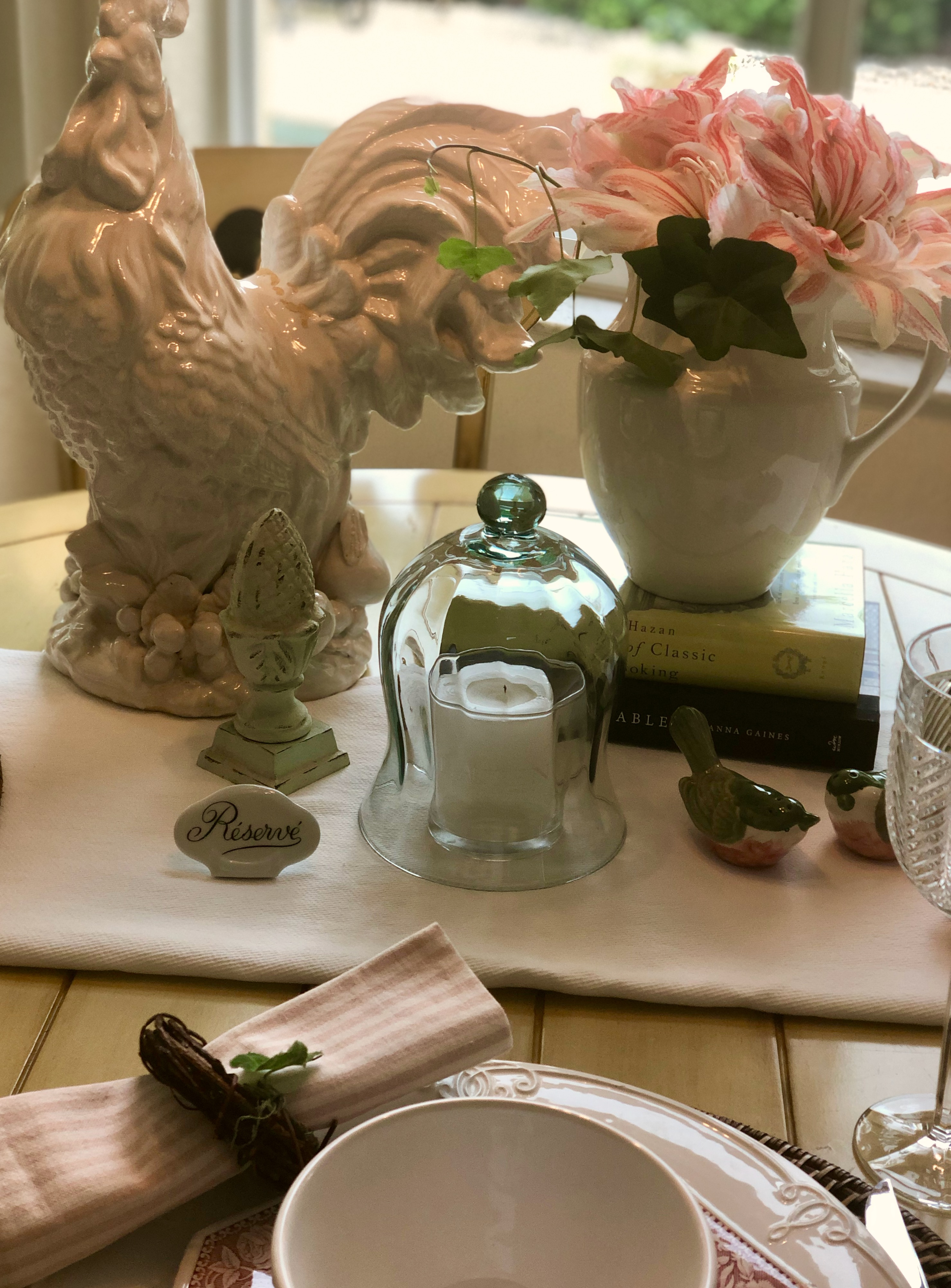 Spring table setting with rooster, pitcher with pink variegated amaryllis, garden finial, bird salt and pepper set and books