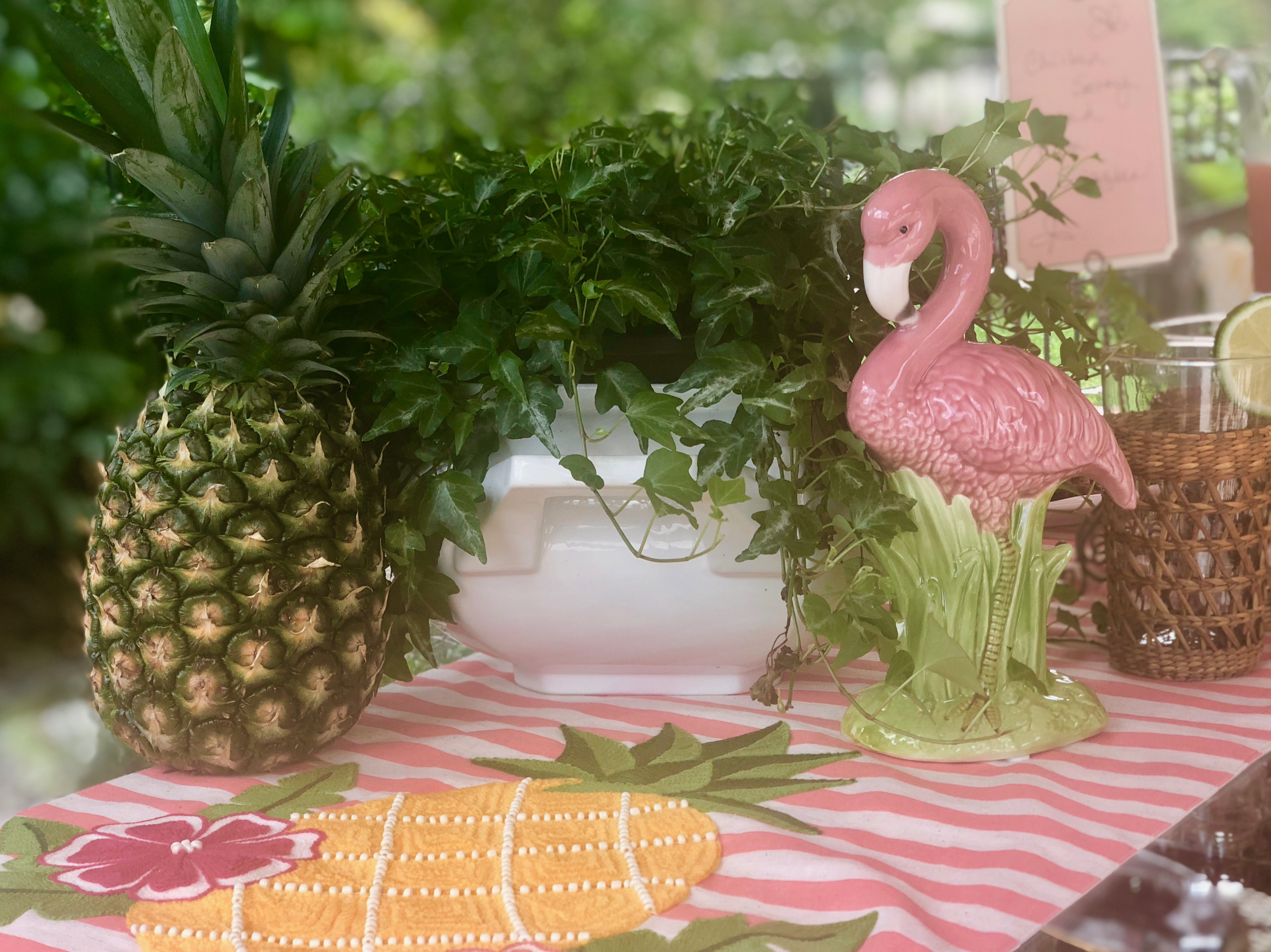 Fresh pineapple with flamingo, ivy plant, rum drink and fun table runner on our patio at the bar