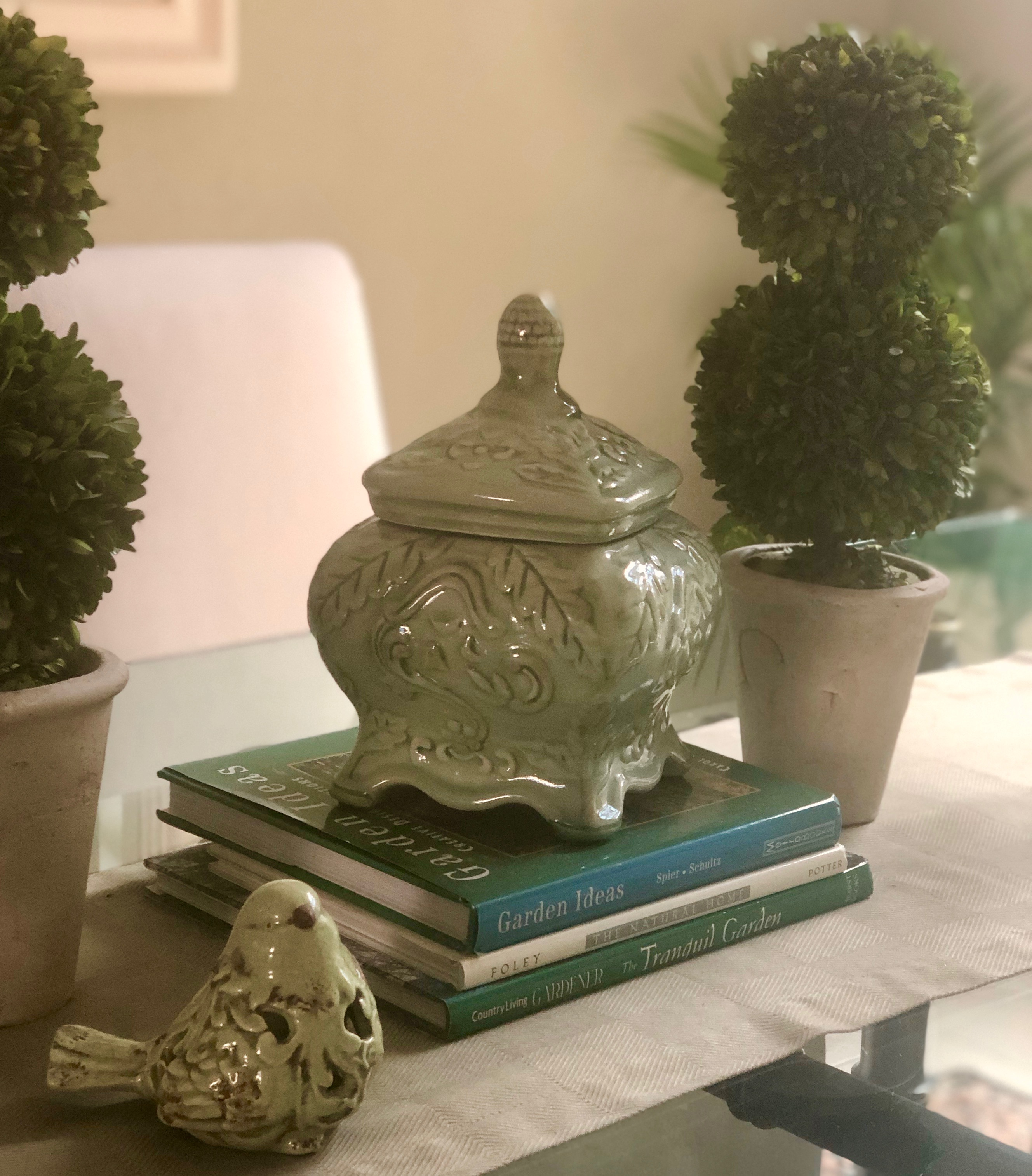 Table with ginger jar, stack of books and topiaries. There is a small green bird in front with a grey/green runner