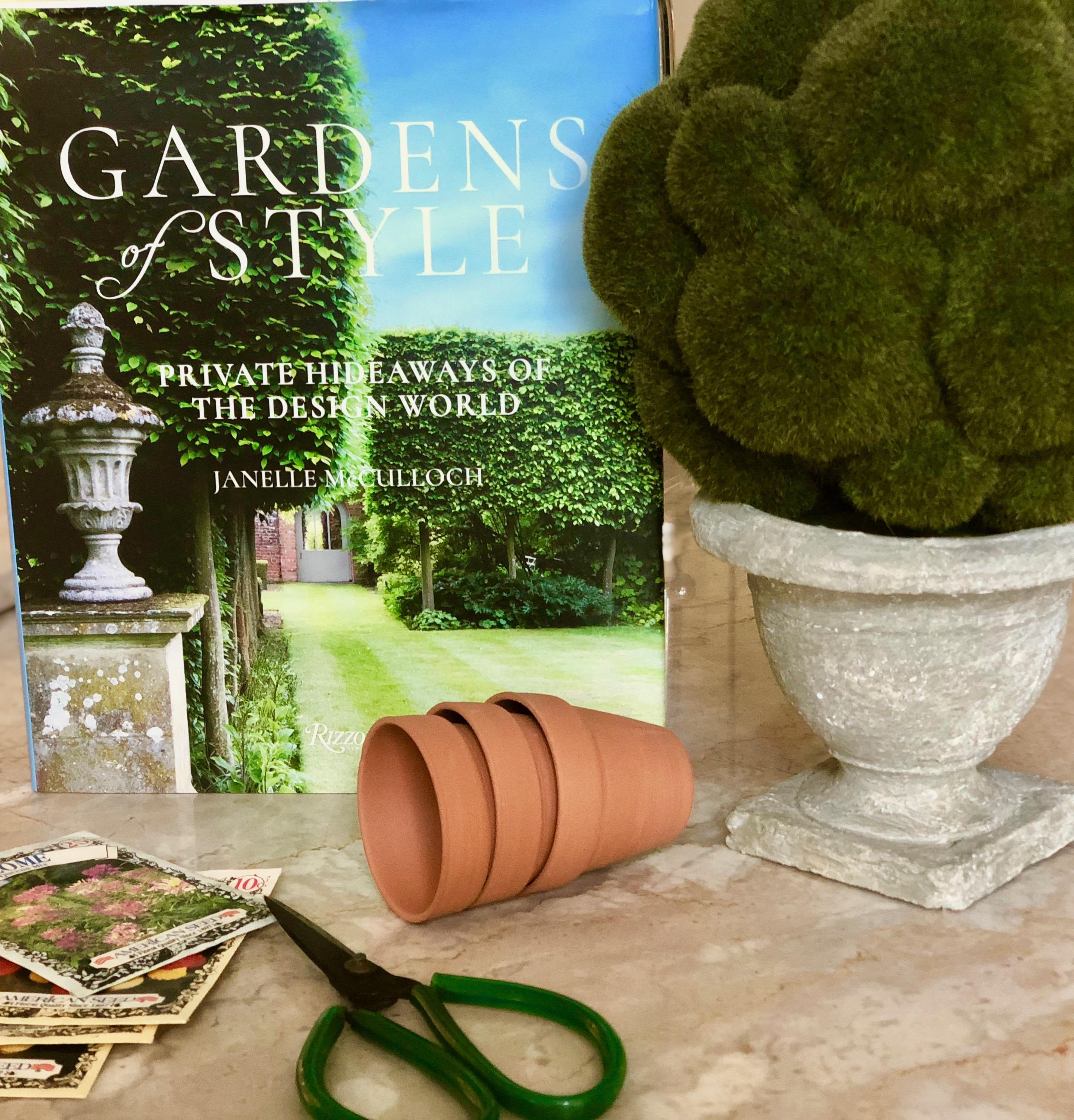 Picture of Gardens of Style Coffee Table book with small flower pots, seed packets and a topiary