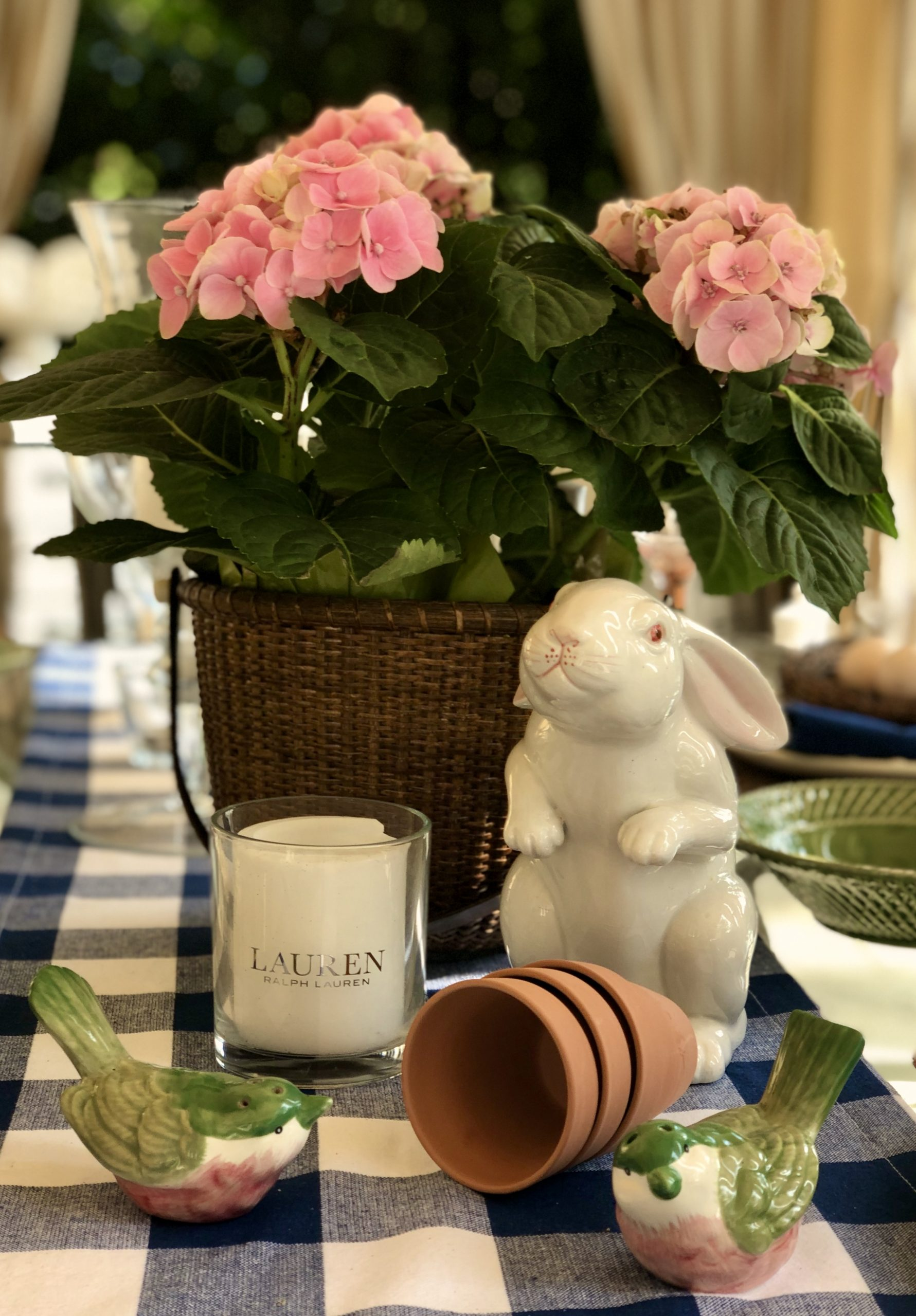 Easter Tablescape With Bundt, Hydrangea In A Basket And Bird Salt And Pepper Shakers. All Set On a Blue And White Buffalo Plaid Table Runner