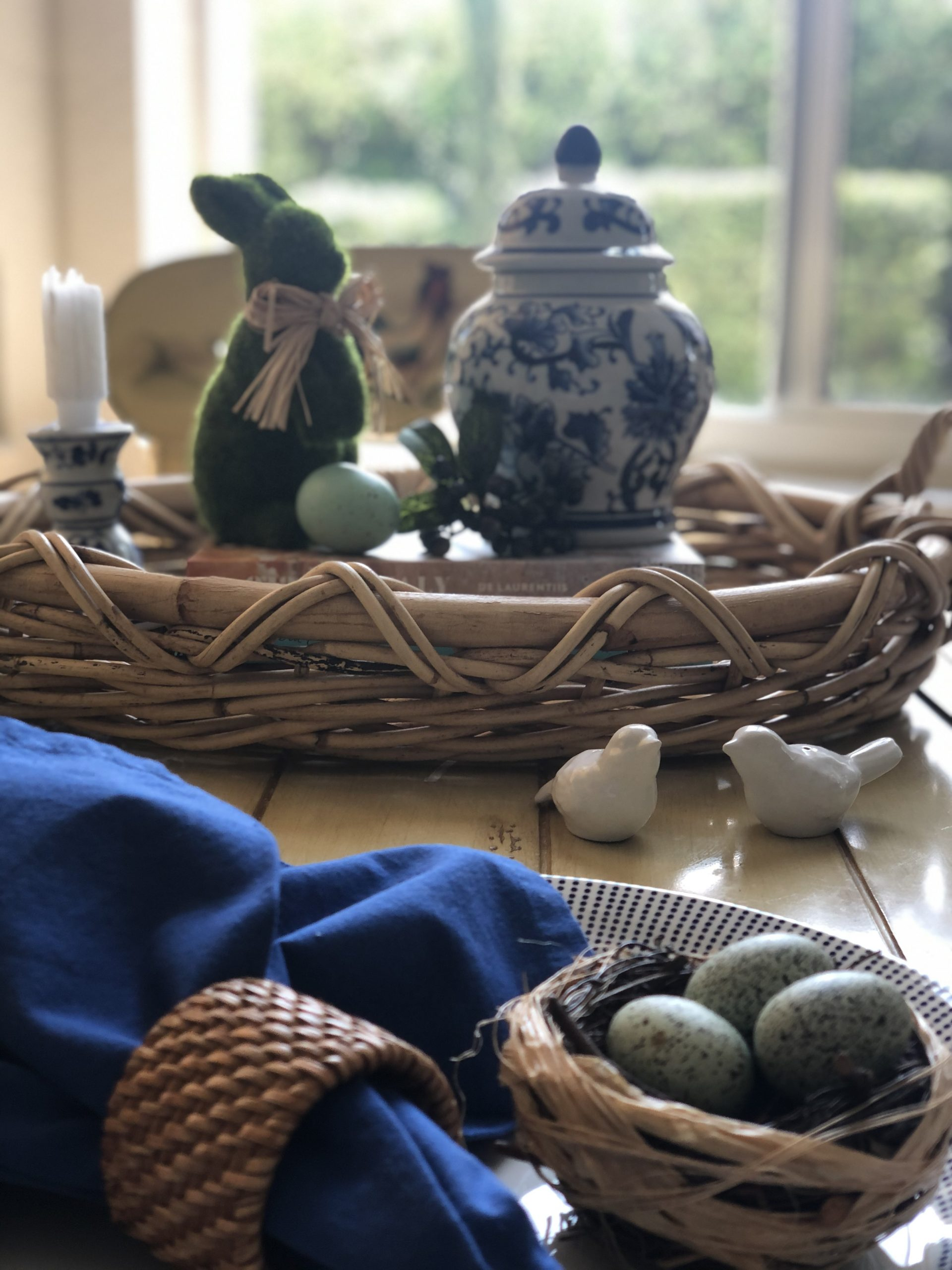 Breakfast Table Setting With Bird Nests With Eggs, Blue And White Ginger Jar, Moss Bunny And Natural Woven Tray And Napkin Rings