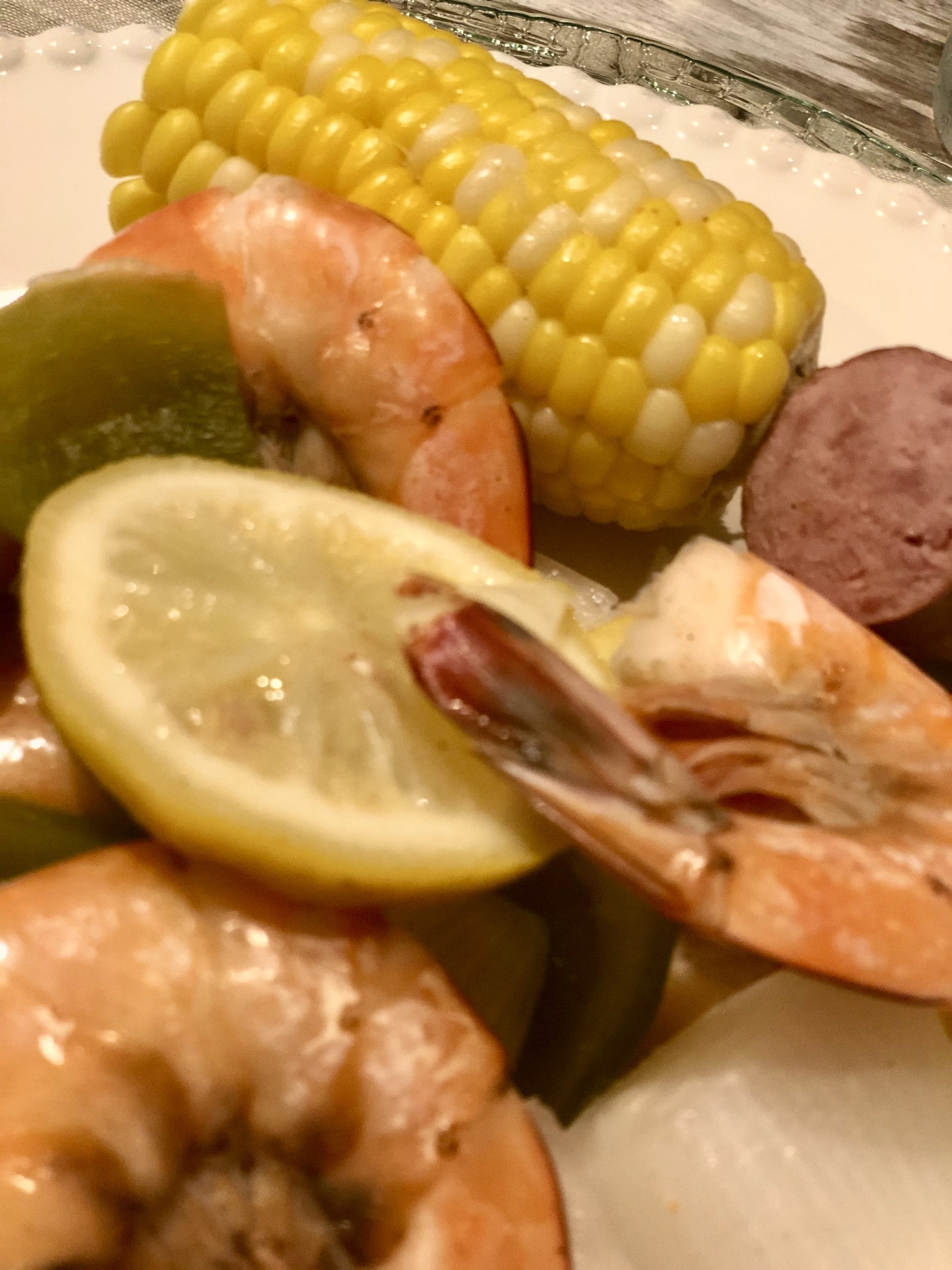 Shrimp boil with lemons, sausage and corn on the cobb